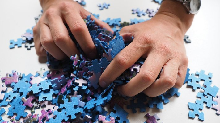 Hands on a collection of blue and purple puzzle pieces