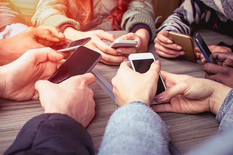 hands on smart phones - a group of friends using mobile phones sitting at the table
