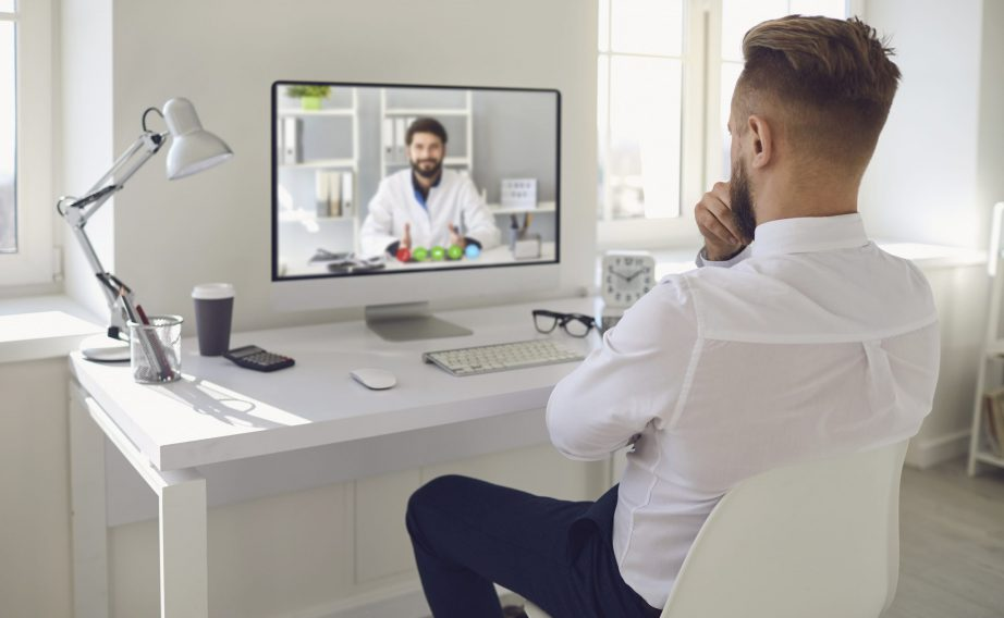 man on computer for telehealth appointment